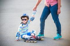 A criança em idade pré-escolar cai sobre ao rollerblading com a mãe no pa Fotos de Stock Royalty Free