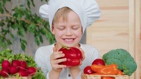 Criança em idade pré-escolar com o chapéu principal que classifica e que explora o alimento saudável filme