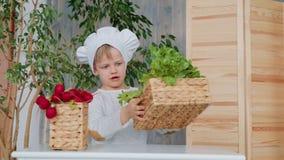 Criança em idade pré-escolar com o chapéu principal que classifica e que explora o alimento saudável video estoque