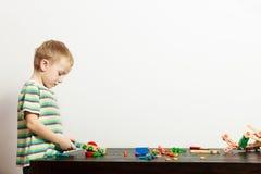 A criança em idade pré-escolar da criança da criança do menino que joga com blocos de apartamentos brinca o interior Imagem de Stock Royalty Free