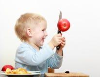 Criança em idade pré-escolar loura da criança da criança do menino com a maçã do fruto do corte da faca de cozinha imagens de stock royalty free