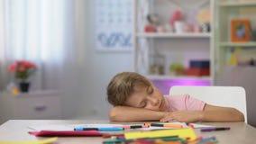 Criança em idade pré-escolar masculina que dorme na mesa, nos lápis da cor e no papel na tabela do jardim de infância video estoque