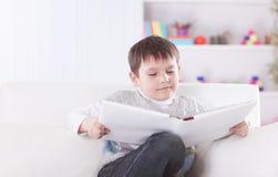 Criança em idade pré-escolar que lê um livro no sofá no berçário foto de stock royalty free