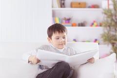 Criança em idade pré-escolar que lê um livro no sofá no berçário imagem de stock royalty free