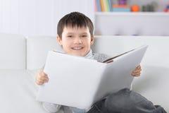 Criança em idade pré-escolar que lê um livro no sofá no berçário fotografia de stock