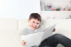 Criança em idade pré-escolar que lê um livro no sofá no berçário imagens de stock
