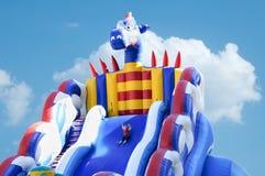 criança em passeios de um parque de diversões com uma montanha russa grande inflável imagens de stock