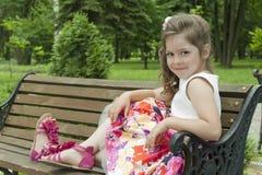 Criança em um banco no parque Fotografia de Stock Royalty Free