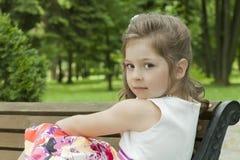 Criança em um banco no parque Foto de Stock