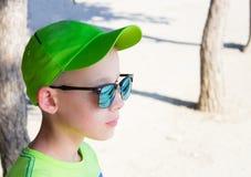 A criança em um boné de beisebol verde e em óculos de sol Foto de Stock