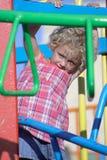 Criança em um campo de jogos Fotos de Stock Royalty Free