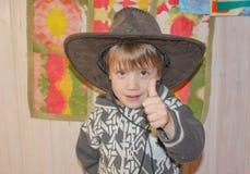 A criança em um chapéu de vaqueiro está sorrindo amplamente Um rapaz pequeno na fotos de stock royalty free