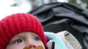 Criança em um chapéu feito malha vermelho e uma chupeta que senta-se em uma cadeira de rodas no outono vídeos de arquivo