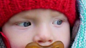 Criança em um chapéu feito malha vermelho e uma chupeta que senta-se em uma cadeira de rodas no outono video estoque