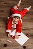 Criança em um terno de Santa Claus que escreve uma letra com desejos para Fotos de Stock Royalty Free