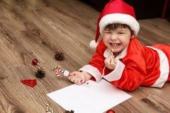 Criança em um terno de Santa Claus que escreve uma letra com desejos para Foto de Stock