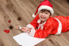Criança em um terno de Santa Claus que escreve uma letra com desejos para Fotografia de Stock