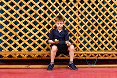 a criança em um uniforme dos esportes senta-se em um banco de madeira e guarda-se uma bola em uma raquete de tênis de mesa no g fotos de stock royalty free