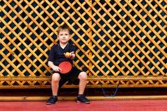 a criança em um uniforme dos esportes senta-se em um banco de madeira e guarda-se uma raquete de tênis de mesa e uma bola no gy foto de stock royalty free
