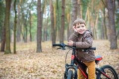 Criança em uma bicicleta na floresta no amanhecer Menino que dá um ciclo o Fotografia de Stock Royalty Free
