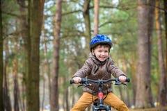 Criança em uma bicicleta na floresta no amanhecer Menino que dá um ciclo o Imagem de Stock
