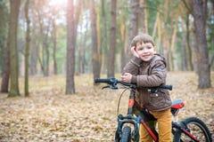 Criança em uma bicicleta na floresta no amanhecer Menino que dá um ciclo o Fotografia de Stock