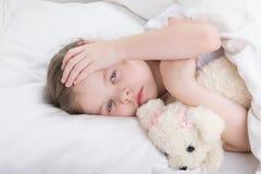 A criança em uma cama branca queixa-se de uma dor de cabeça fotografia de stock royalty free