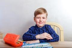 Criança em uma camisa escura que senta-se em uma mesa fotografia de stock royalty free