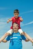 Criança em uma camisa vermelha que senta-se em seu pai Foto de Stock