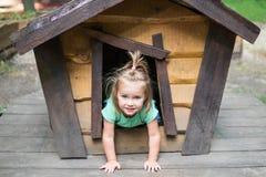 Criança em uma casa de cachorro Foto de Stock