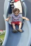 Criança em uma corrediça Fotos de Stock