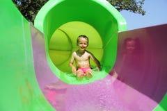 Criança em uma corrediça de água Fotos de Stock Royalty Free