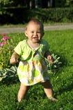 Criança em uma grama Foto de Stock Royalty Free