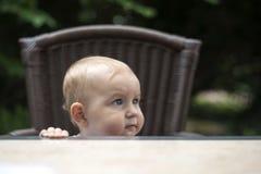 A criança em uma tabela em um restaurante espera um garçom Foto de Stock