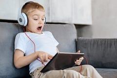 Criança emocional encantador que olha algo excitar em sua tabuleta fotos de stock royalty free