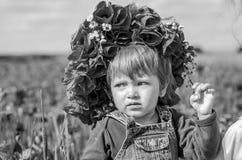 Criança encantador do bebê bonito pequeno da menina na grinalda da papoila de campo de ação do vestido das calças de brim com um  Fotografia de Stock Royalty Free