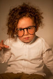 Criança encaracolado bonito com os monóculos que olham a câmera Imagens de Stock Royalty Free
