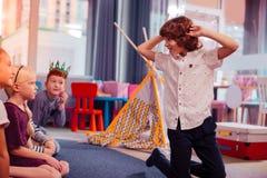 Criança encaracolado-de cabelo brincalhão que faz as caras durante o jogo fotos de stock royalty free