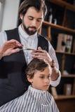criança encaracolado que obtém o corte de cabelo imagem de stock