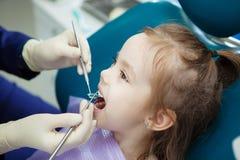 A criança encontra-se na cadeira do dentista e o doutor faz o controle Fotos de Stock