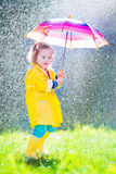 Criança engraçada com o guarda-chuva que joga na chuva Foto de Stock