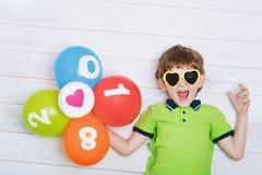 A criança engraçada com os óculos de sol, guardando balões do arco-íris encontra-se no th Imagens de Stock