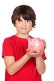 Criança engraçada com piggy-banco cor-de-rosa Imagens de Stock