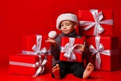 Criança engraçada de sorriso no chapéu vermelho de Santa que mantém o presente do Natal disponivel Conceito do Natal foto de stock royalty free