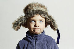 Criança engraçada no chapéu forrado a pele estilo ocasional do inverno da forma Little Boy imagens de stock