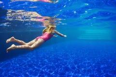 A criança engraçada nos óculos de proteção mergulha na piscina imagem de stock royalty free
