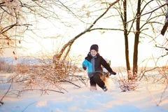 Criança engraçada pequena bonito na roupa do inverno que tem o divertimento com neve, fora durante a queda de neve Crianças ativa imagens de stock royalty free