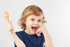 Criança engraçada pequena que guardara a colher de madeira Imagem de Stock Royalty Free
