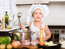 Criança engraçada que cozinha a sopa com vegetais Imagens de Stock