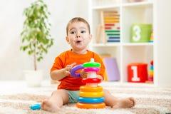 Criança engraçada que joga com o brinquedo da cor interno Imagens de Stock Royalty Free